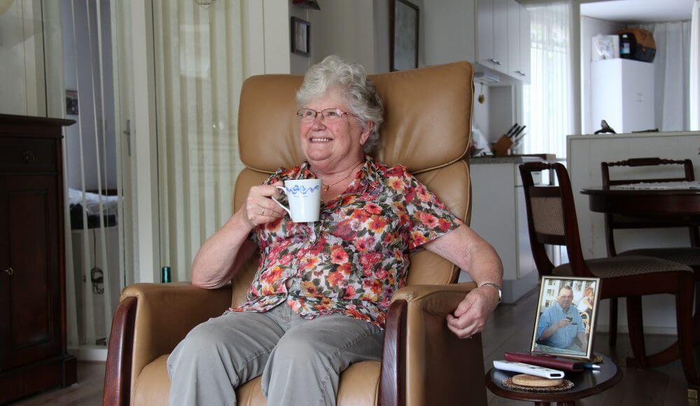Tevreden client in haar woonkamer met kopje koffie